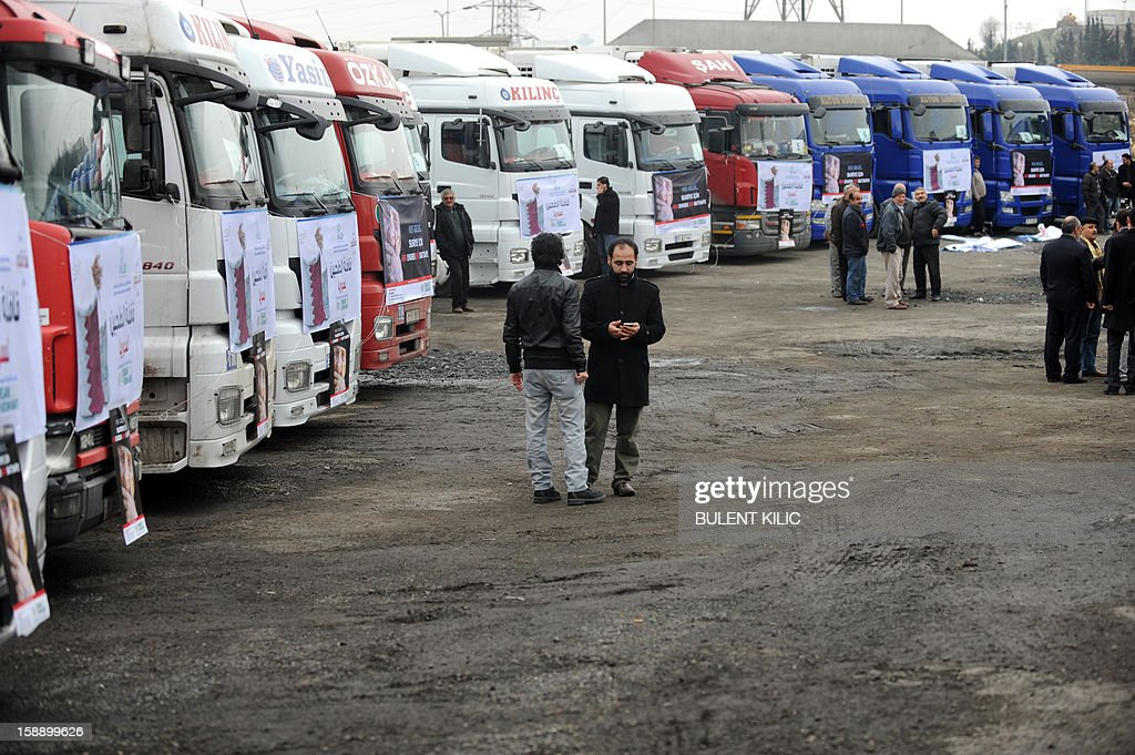 People stand in front of supply trucks of the Foundation for Human Rights and Freedoms and Humanitarian Relief (IHH) on January 3, 2013 in Istanbul. IHH Humanitarian Relief Foundation sent 850 tons of flour to Syria. 'Bread&Blanket for Syria' campaign is supported by nearly 200 NGOs including Union of Civil Society Organizations of the Islamic World, Independent Industrialists and Businessmen Association of Turkey (MUSIAD), Turkish Volunteer Institutions Foundation, Humanitarian Aid Foundation (IHH), Deniz Feneri Association, Cansuyu Aid Association, Yardimeli Association, Ensar Foundation, Verenel Association and Istanbul International Brotherhood and Assistance Association.