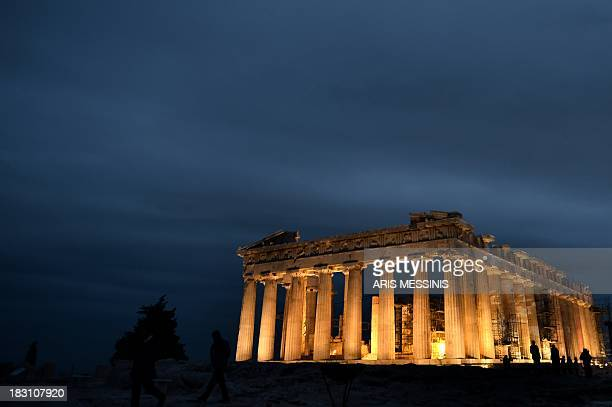 People stand in front of the ancient Temple of Parthenon atop the Acropolis hill on October 4 2013 AFP PHOTO / ARIS MESSINIS