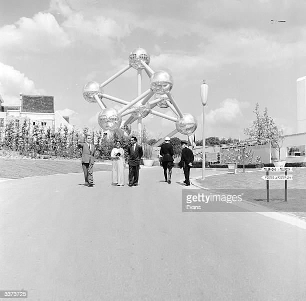 People stand in front of the Atomium the symbol of the World's Fair in Brussels Belgium