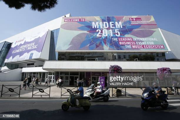 People stand in front of the entrance of the music world's largest annual trade fair MIDEM on June 5 2015 at the Palais des Festivals in Cannes...