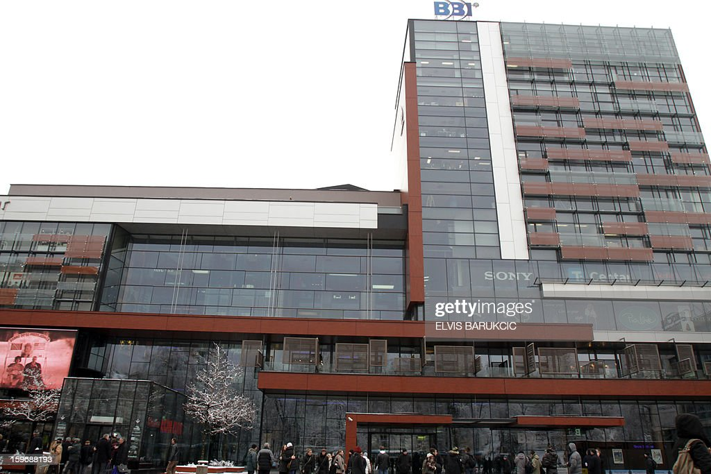 People stand in front of the Entrance to the 'BBI' shopping mall in the business center of Sarajevo after a bomb threat has been called in, on January 18, 2013. The mall has been evacuated and the police bomb experts have been called to inspect the building.