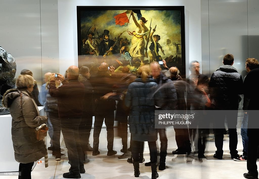 People stand in front of the Eugene Delacroix masterpiece 'La Liberté guidant le Peuple' (Liberty leading the people) at the Louvre Museum on the first day of its opening to the public on December 4, 2012 in Lens, northern France. The Louvre museum opened a new satellite branch among the slag heaps of a former mining town Tuesday in a bid to bring high culture and visitors to one of France's poorest areas. Greeted by a group of former miners in overalls and hardhats, President Francois Hollande inaugurated today the Japanese-designed glass and polished-aluminium branch of the Louvre in the northern city of Lens. The 150 million euro ($196 million) project was 60 percent financed by regional authorities in the Nord-Pas-De-Calais region, on the English Channel and the border with Belgium.