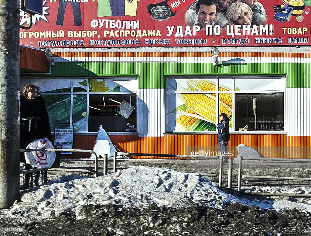 People stand in front of the facade of a local shop which was damaged by a shockwave from a meteor in the Urals city of Chelyabinsk, on February 15, 2013. A meteor strike in central Russia that left today hundreds of people injured is the biggest known human toll from a space rock, a British expert said.