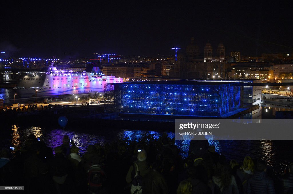 People stand in front of the future Museum of Civilisations from Europe and the Mediterranean (MUCEM) designed by Italian architect Rudy Ricciotti (at center) as they attend on January 12, 2013 in the French southern city of Marseille, the light parade, part of the launching of Marseille-Provence 2013 European Capital of Culture. The event marks the start of a year, leading to a cultural renaissance in France's second-largest metropolitan area. AFP PHOTO / GERARD JULIEN