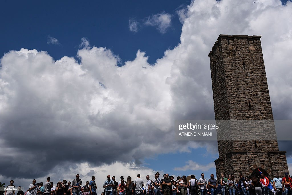 People stand in front of the Gazimestan memorial, near the village of Mazgit, Kosovo, as they take part in a ceremony marking the historic 'Battle of Kosovo', on June 28, 2016. The ceremony marks the Battle of Kosovo in 1389 when the Serbian army was defeated by the Ottoman Empire. / AFP / ARMEND