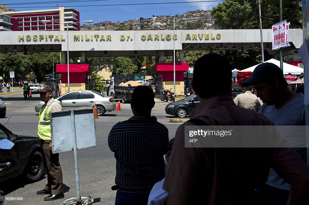 People stand in front of the military hospital in Caracas where Venezuelan President Hugo Chavez has been hospitalized following his return from Cuba, on February 25, 2013. The mystery surrounding the president's health has cast doubt over the political future of a nation sitting on top of the world's biggest oil reserve. AFP PHOTO/ Leo RAMIREZ