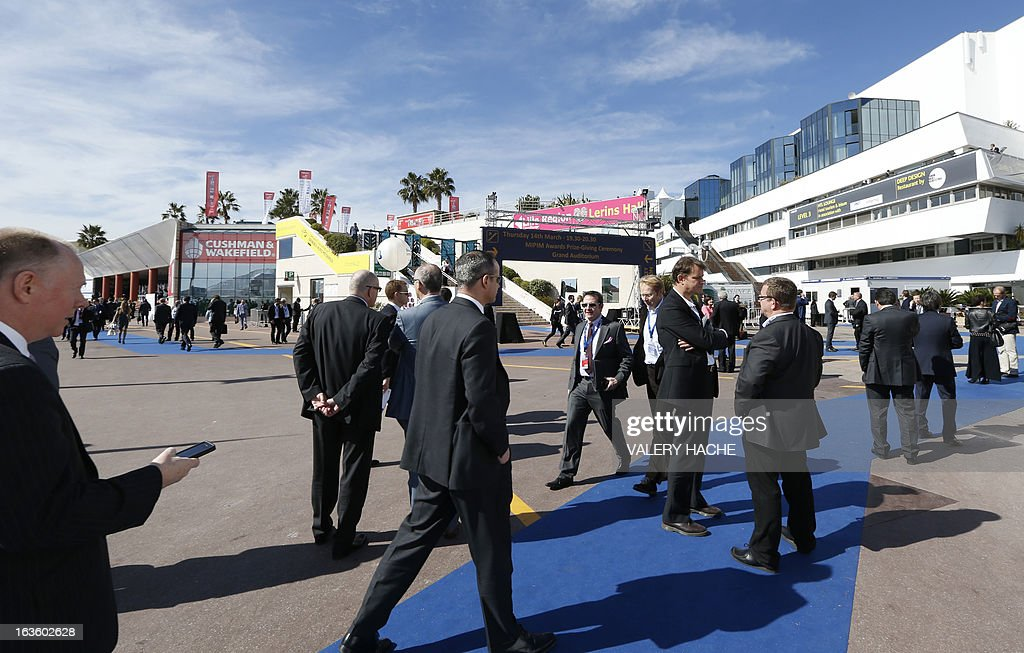 People stand in front of the Palais des Festivals on March 13, 2013 in Cannes, southeastern France, during the MIPIM, an international real estate show for professionals. The event takes place until March 15. AFP PHOTO / VALERY HACHE