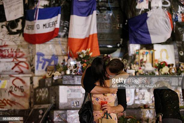 TOPSHOT People stand in front of the place de la Republique's monument in Paris on July 26 2016 after a priest was killed in the Normandy city of...