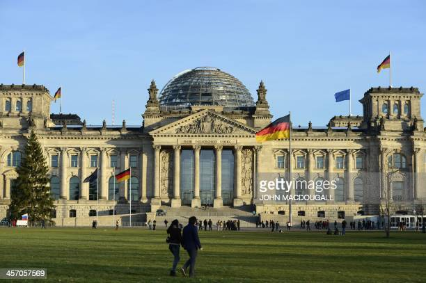 People stand in front of the Reichstag building housing the German parliament Bundestag on December 16 2013 on the eve of the swearingin ceremony of...
