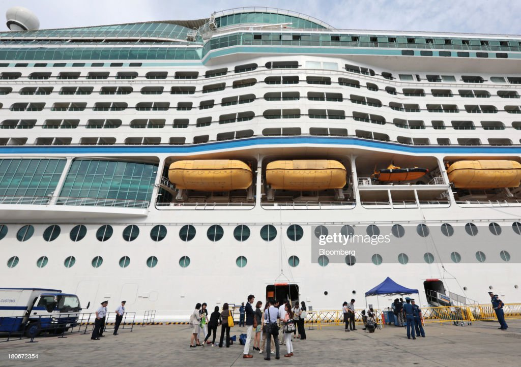 People stand in front of the Royal Caribbean Cruises Ltd.'s Voyager of the Seas, berthed at the Ohi wharf in Tokyo, Japan, on Saturday, Sept. 14, 2013. Royal Caribbean, the worlds second-largest cruise-line operator, doubled its dividend and will make directors stand for election every year. Photographer: Yuriko Nakao/Bloomberg via Getty Images