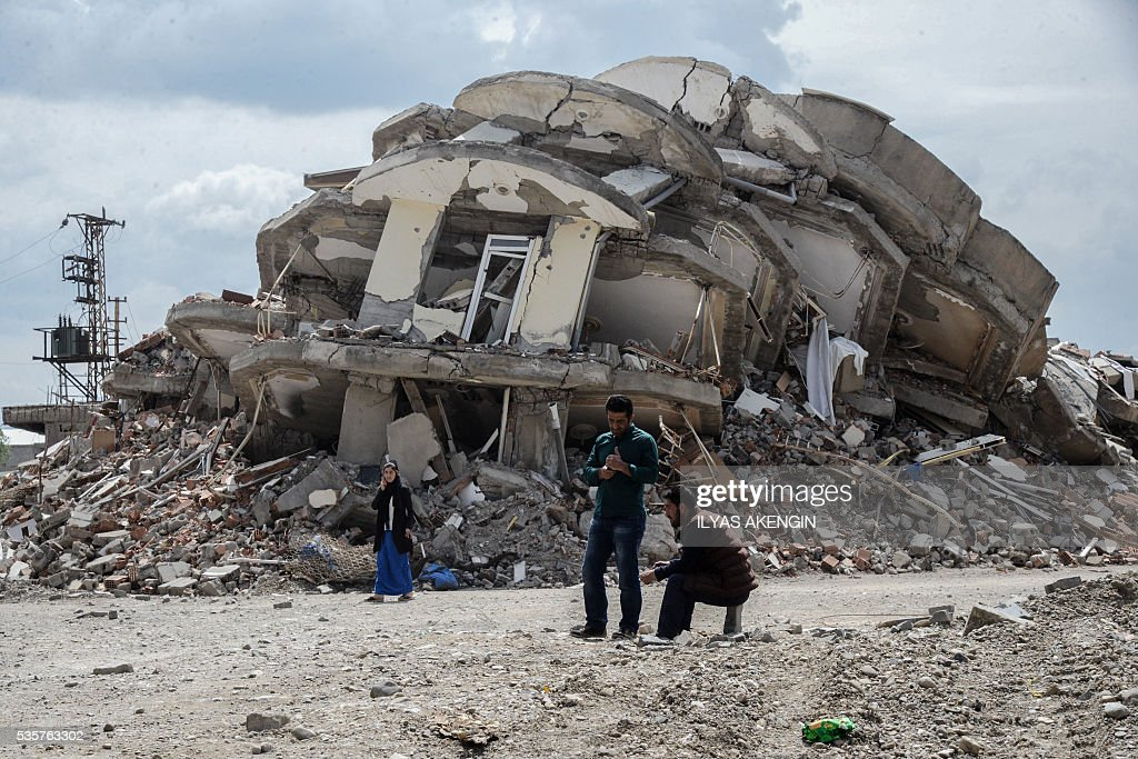 TOPSHOT People stand in front of the rubbles of a damaged building after heavy fightings between Turkish government troops and Kurdish fighters after...
