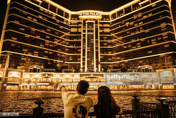 People stand in front of Wynn Resorts Ltd's Wynn Palace casino resort at night in Macau China on Sunday Aug 28 2016 Macau is scheduled to release...