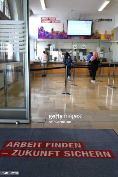 People stand in line at a Jobcenter in DuesseldorfMitte western Germany on August 25 2017 The number of people out of work has halved in Germany...