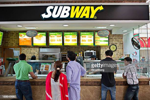 People stand in line at a Subway fast food restaurant at the AlphaOne shopping mall in Amritsar India on Thursday May 9 2013 India's consumer price...