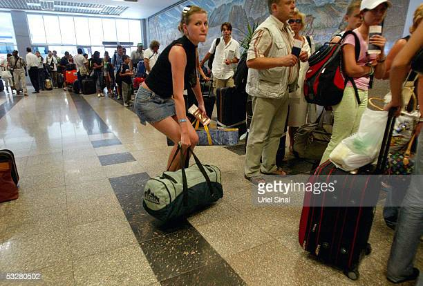 People stand in line at an airport on there way out July 24 2005 in the resort town of Sharm elSheik Egypt A rapid series of explosions killed over...