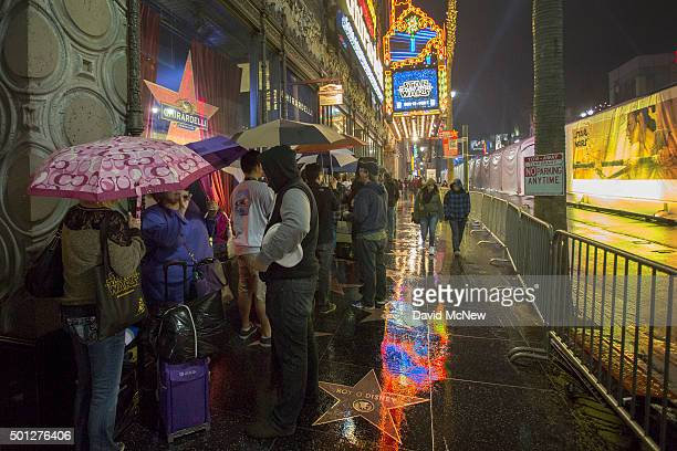 People stand in line in the rain outside of the Disney Studio Store and Ghirardelli Soda Fountain and Chocolate Shop next to the El Capitan Theatre...