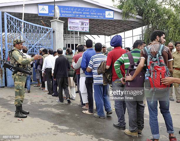 People stand in line outside the airport to be flown out by the Indian Air Force on September 9 2014 in Srinagar India More than 50000 people have...