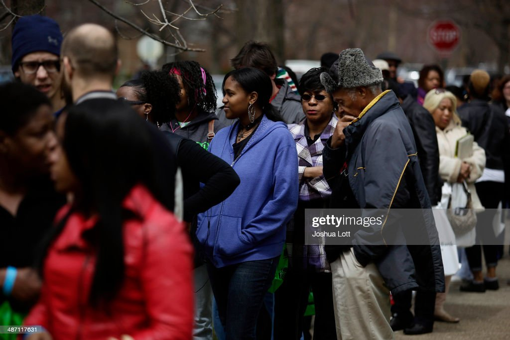 People stand in line to board a bus before touring one of twelve homes being auctioned off in the East English Village neighborhood April 27, 2014 in Detroit, Michigan. The city of Detroit and the Detroit Land Bank will auction off 12 homes starting May 5. One home will be auctioned off per day with an opening bid of $1,000.