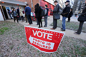 People stand in line to cast their votes at the polling place inside the Arlington County Fire Station 10 during Super Tuesday voting March 1 2016 in...