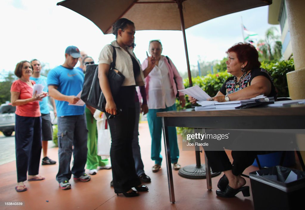 People stand in line to deliver their voter registration forms to a MiamiDade Elections Department officials on the final day for voters to register...