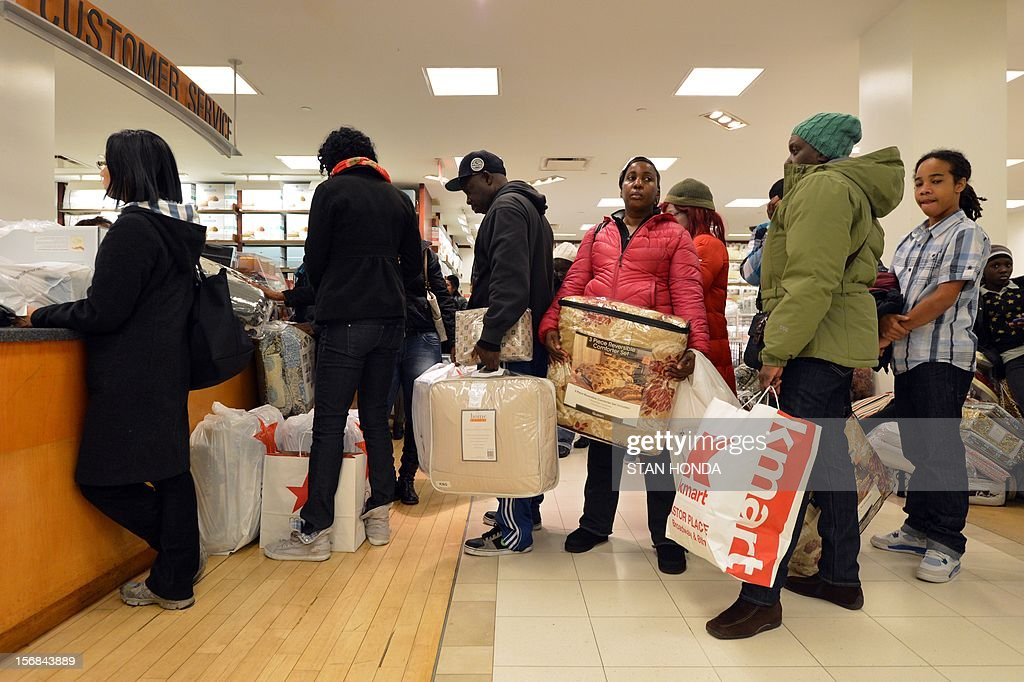 People stand in line to make purchases in Macy's department store as they open at midnight (0500 GMT) on November 23, 2012 in New York to start the stores' 'Black Friday' shopping weekend. AFP PHOTO/Stan HONDA
