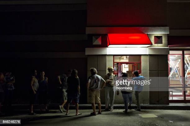People stand in line to order food at the drive through window of an Arby's restaurant in Estero Florida US on Tuesday Sept 12 2017 With limited...
