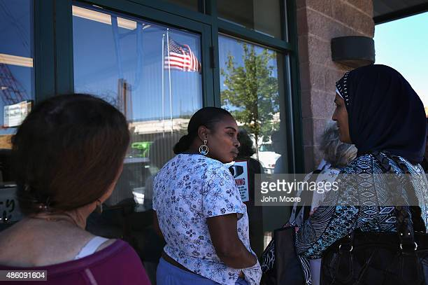 People stand in line to receive fresh bread and produce at the Community Food Bank of New Jersey on August 28 2015 in Egg Harbor New Jersey The food...