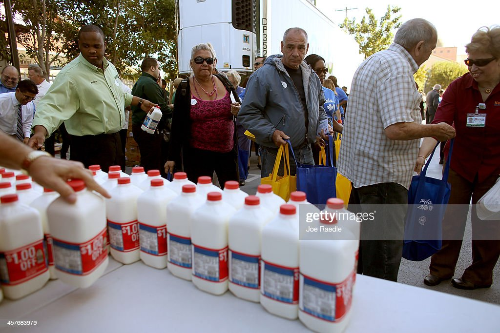People stand in line to receive their holiday grocery supplies from the Latin American Chamber of Commerce on December 18, 2013 in Miami, Florida. The chamber handed out 3,000 vouchers during the annual event several weeks ago and those with vouchers exchanged them today for bags of food worth up to $250. The meals include pork, yucca, milk, soda, and bread along with other items.