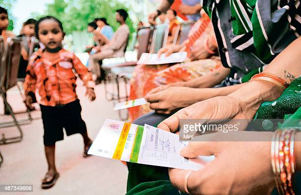People stand in queue during Aadhar card camp pilot project for authentication of UID cards at Kalyanpuri on April 12 2013 in New Delhi India