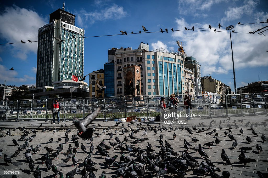 People stand in Taksim square in Istanbul during May Day rally, on May 1, 2016. Turkish labour activists and leftists marked the annual May Day holiday, with thousands of security deployed and bracing for trouble after the authorities refused to allow protests in central Taksim Square. / AFP / OZAN