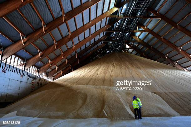 People stand in the French sugar cooperative Cristal Union's storage area at the SFIR Raffineria di Brindisi sugar refinery in Brindisi on March 15...