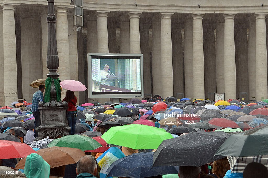 People stand in the rain and watch Pope Francis on a giant screen at St.Peter's square during the Sunday Angelus prayer on September 15, 2013.
