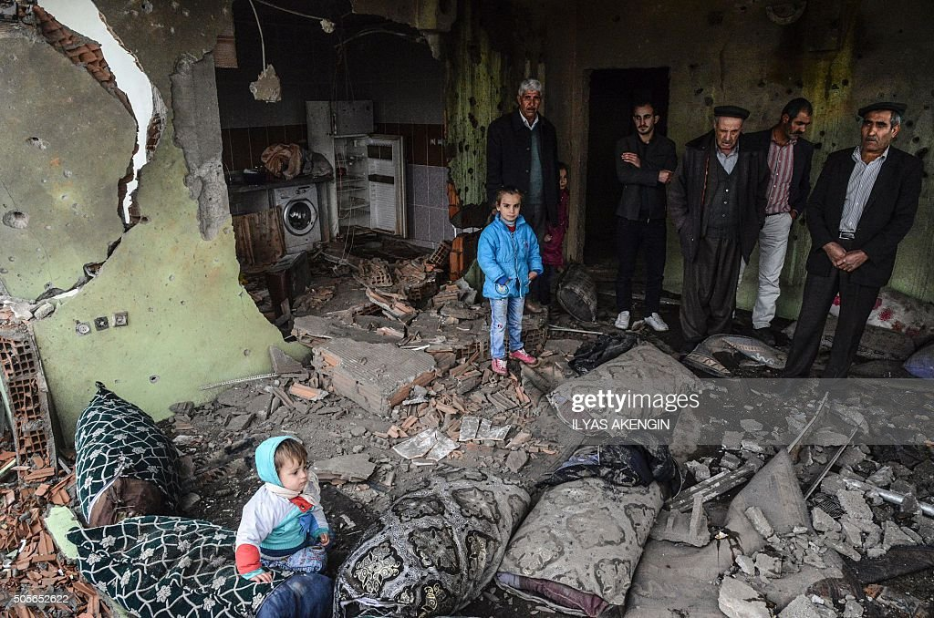 TOPSHOT People stand in the ruins of an house as curfew ends during daylight in the town of Silopi on January 19 2016 Turkey is waging an allout...