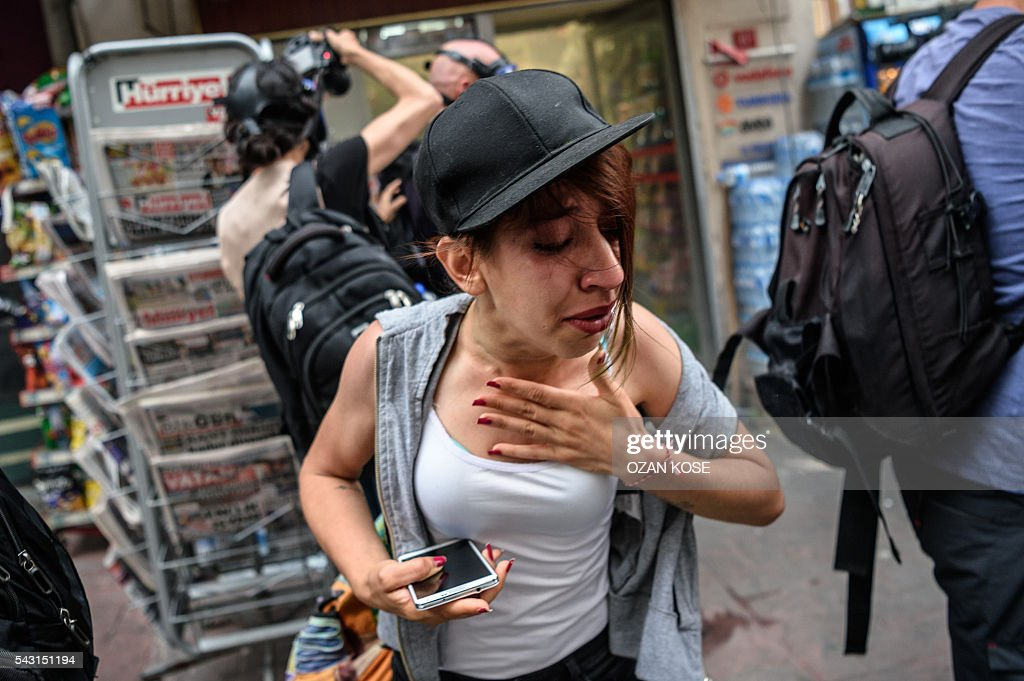 People stand in the street as Turkish anti riot police officers fired rubber bullets and tear gas to disperse demonstrators gathered for a rally staged by the LGBT community on Istiklal avenue in Istanbul on June 26, 2016. Riot police fired tear gas and rubber bullets to disperse protesters defying a ban on the city's Gay Pride parade. Authorities in Turkey's biggest city had banned the annual parade earlier this month citing security reasons, sparking anger from gay rights activists. KOSE