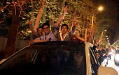 People stand in the sunroof of a car and flash the 'V for Victory' sign as they celebrate on Valiasr street in northern Tehran on April 2 after the...