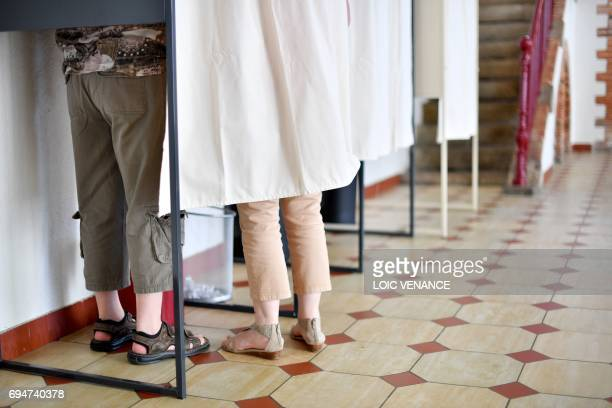 People stand inside a voting booth at a polling station in ChateauThebaud western France during the first round of the French legislative elections...