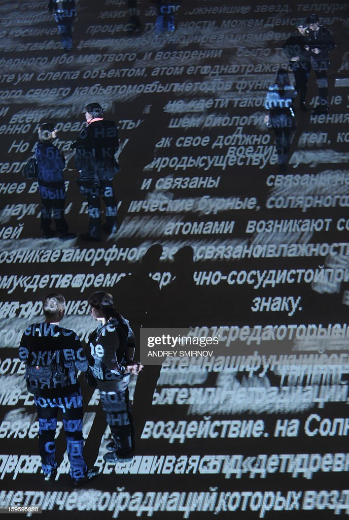People stand inside the Manezh exhibition hall lit by Britain's artist Charles Sandison light work during 'Terrestrial Echo of Solar Storms' installation in Moscow, late on January 16, 2012. Sandison is well known for his projects with the words and letters that come to life, move and die. Movement implement computer programs, which the artist writes specifically for each individual installation.