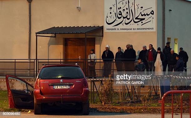 People stand near a car in front of the mosque of Valence southeastern France on January 1 after a soldier guarding the mosque shot and wounded a...