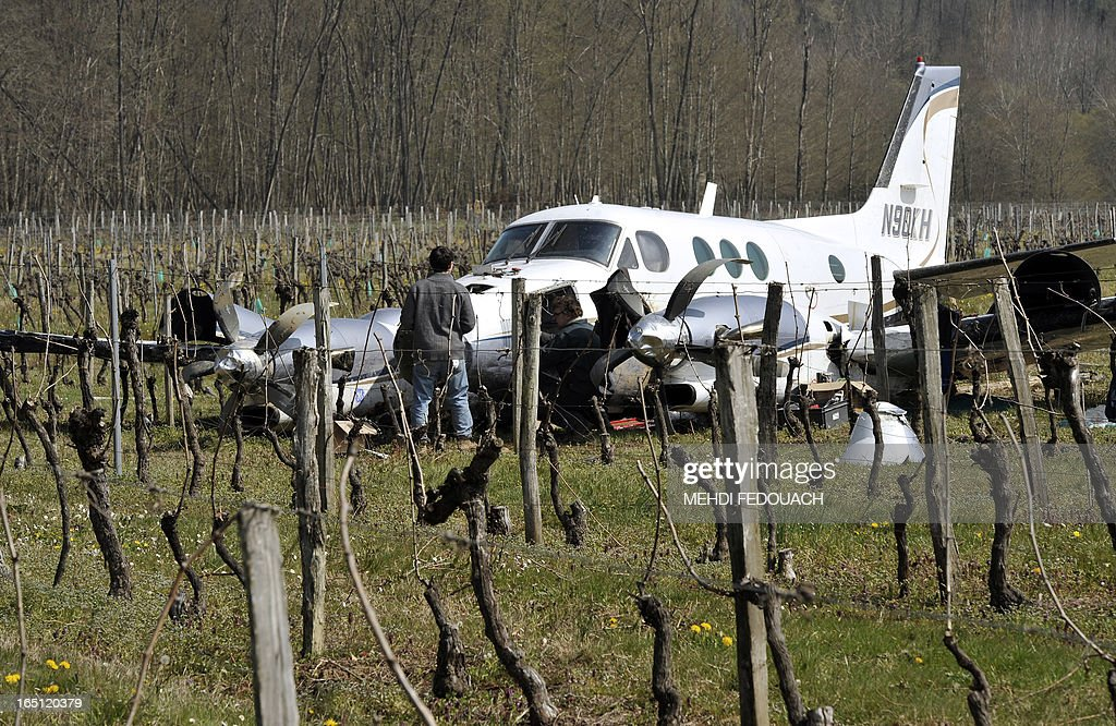 People stand near a damaged Beechcraft 90 resting in a vinyard on March 31, 2013 near Sainte-Radegonde in France's south west after the pilot was forced to land among the vines following a mechanical problem after mid-day on March 29. The pilot and passenger who were travelling back to their Dordogne base walked away from the accident.