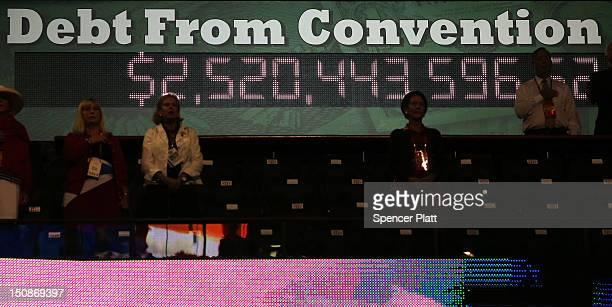 People stand near a display showing the national debt acquired since the convention open during the Republican National Convention at the Tampa Bay...