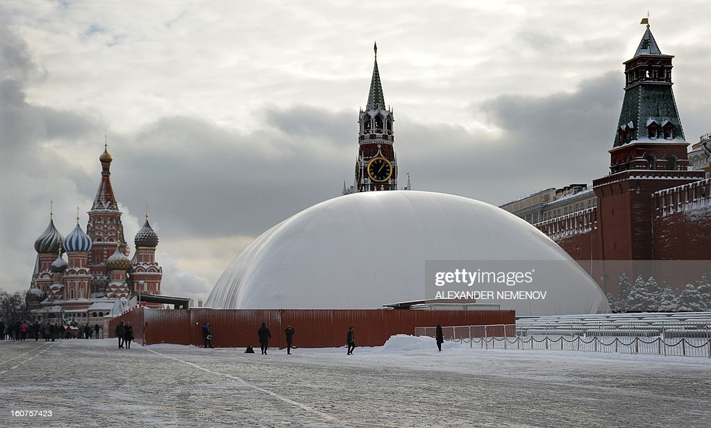 People stand near a huge temporary dome covering the mausoleum of Soviet state founder Vladimir Lenin on Red Square in Moscow, on February 5, 2013. The dome keeps temperatures inside warmer and allows repair works on the mausoleum to continue even during winter to finish them by the end-of-April deadline.