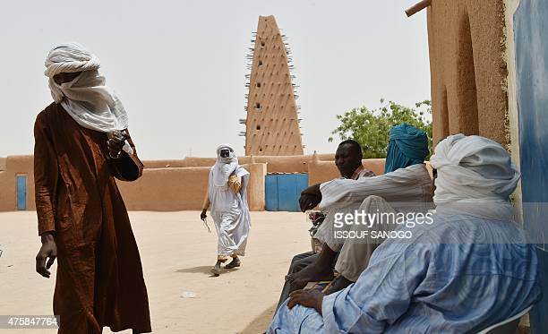 People stand near a mosque in a neighbourhood of the city of Agadez northern Niger on May 31 2015 AFP PHOTO / ISSOUF SANOGO