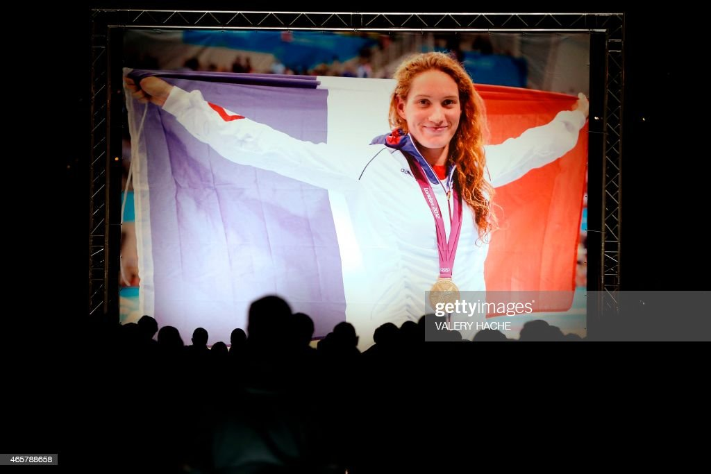 People stand near a picture of French gold medallist Camille Muffat on March 10 2015 in her hometown the southeastern French city of Nice during a...