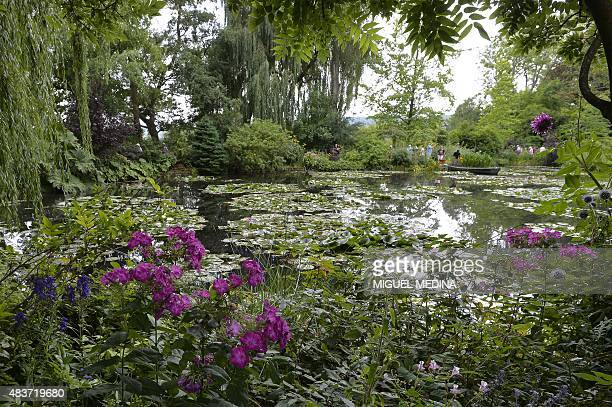 People stand near a pond with lilypads as they visit the gardens of the home of French Impressionist painter Claude Monet in Giverny northwestern...
