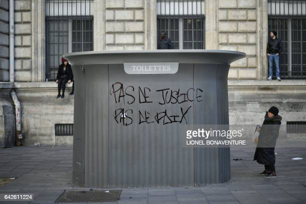 People stand near a pulic toilet bearing a graffiti reading 'No justice no peace' during a demonstration against police brutality on February 18 2017...