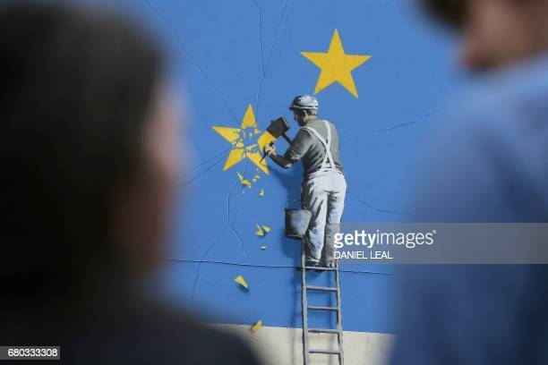 People stand near a recently painted mural by British graffiti artist Banksy depicting a workman chipping away at one of the stars on a European...