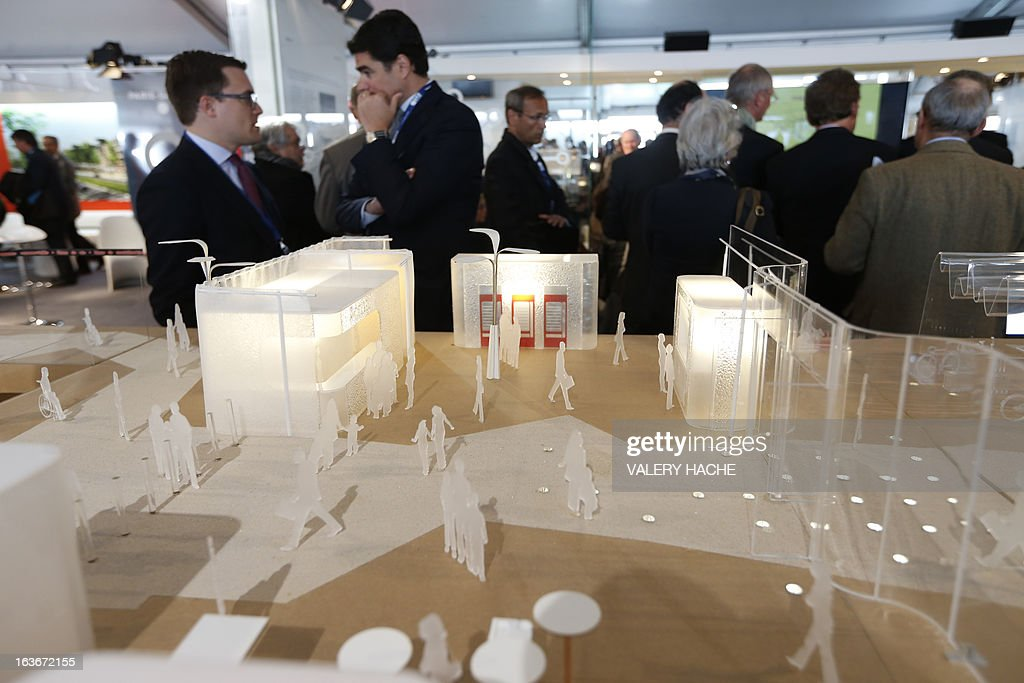 People stand near a scale model of the 'Gares du Grand Paris' project on March 14, 2013 at the Palais des Festivals in Cannes, southeastern France, where takes place the MIPIM, an international real estate show for professionals. The event takes place until March 15.