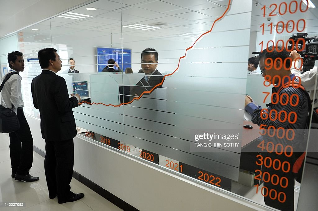 People stand near a stocks graph during a launching ceremony at the Cambodian Securities Exchange (CSX) in Phnom Penh on April 18, 2012. The Cambodia Securities Exchange (CSX) finally began trading shares on April 18, nine months after it officially opened, when a water monopoly became the first firm to list.