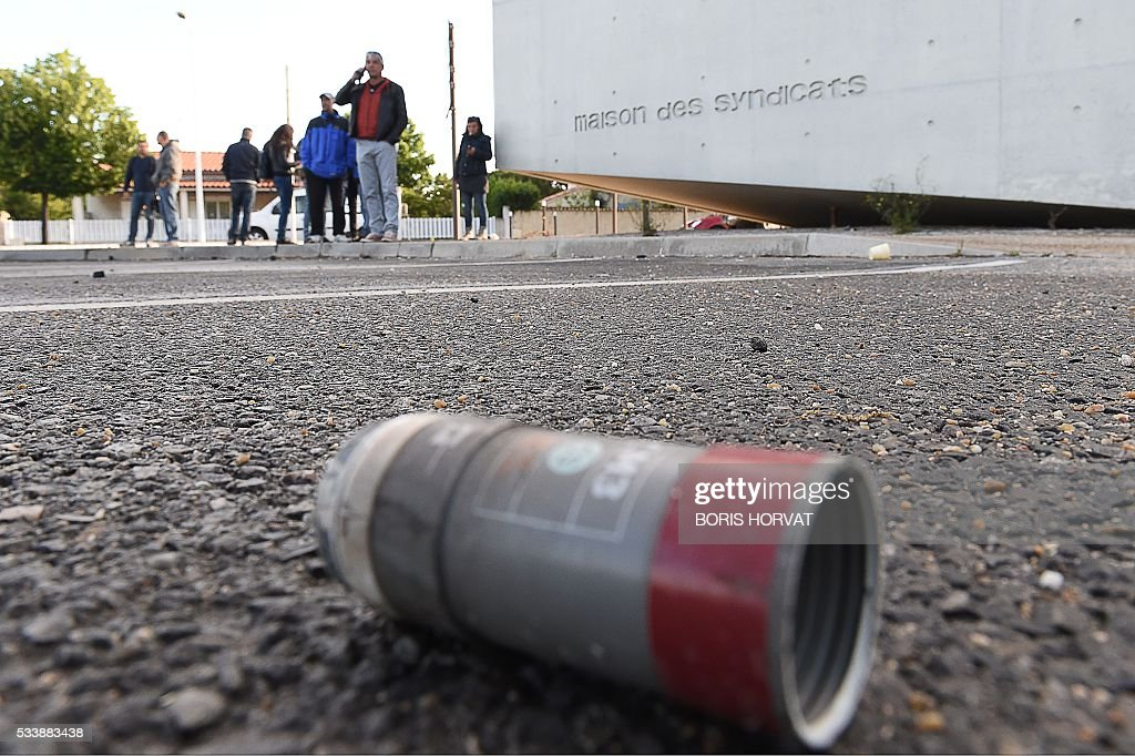 People stand near a tear gas canister on the ground nearby the house of unions at the Esso oil refinery in Fos-sur-Mer, southeastern France, on May 24, 2016, after police evacuated the site which was blockaded by protesters opposed to government labour reforms. Petrol shortages caused long tailbacks of motorists in parts of France on May 23 as protesters angry over government labour reforms blockaded some of the country's oil refineries and fuel depots. The action was the latest in three months of strikes and protests against the reform, which has set the Socialist government against some of its traditional supporters and sometimes sparked violence. HORVAT