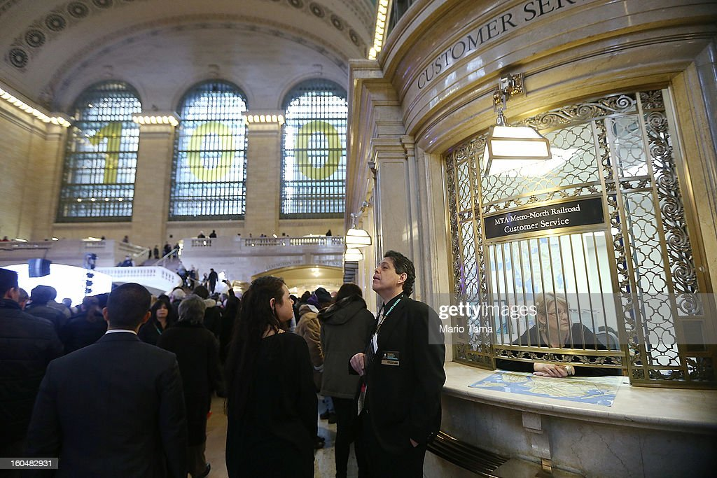 People stand near a ticket window in Grand Central Terminal beneath a '100' sign during centennial celebrations on the day the famed Manhattan transit hub turns 100 years old on February 1, 2013 in New York City. The terminal opened in 1913 and is the world's largest terminal covering 49 acres with 33 miles of track. Each day 700,000 people pass through the terminal where Metro-Noth Railroad operates 700 trains per day.